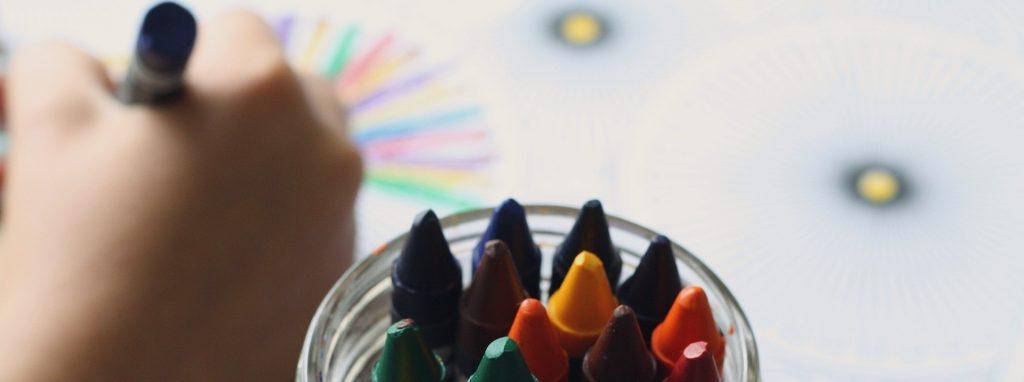 Niño dibujando con ceras de colores